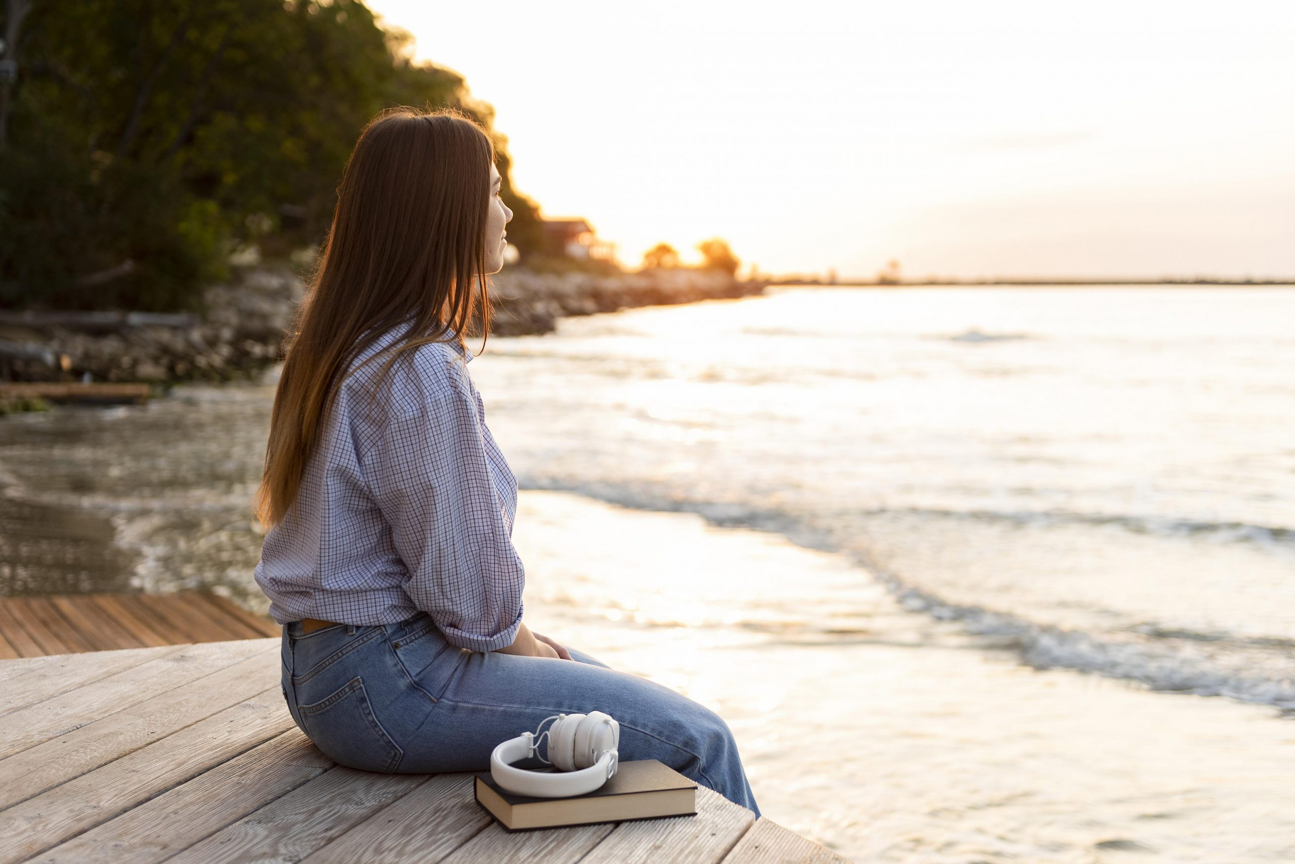 side-view-woman-looking-at-the-sea-at-sunset
